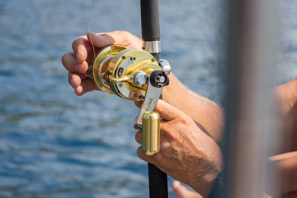 person holding gold fishing reel